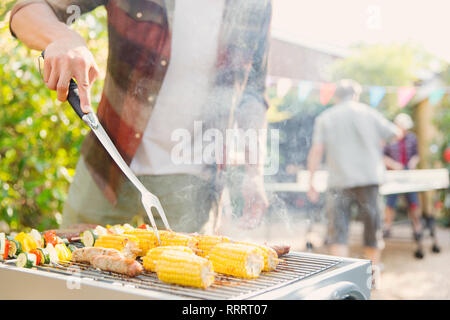 Man barbecuing corn, sausage and vegetable kebabs - Stock Image