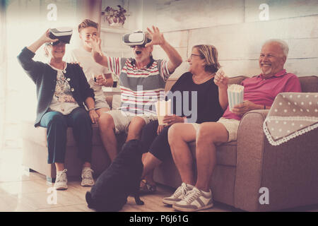 Group of people laughing and enjoying virtual reality. Two senior couples and a teenager eating popcorn. Grandparents and nephew - Stock Image