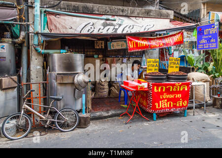 Bangkok, Thailand - 7th March 2017: Man selling roasted chestnuts in Chinatown, Chestnuts are a popular snack. - Stock Image