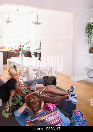 Young women friends hanging out, using smart phones on apartment sofa - Stock Image