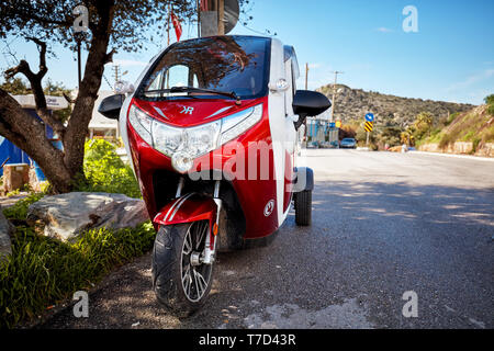 Bodrum, Turkey - January, 2019: Cute small tricycle electric car parked near the asphalt road. Editorial. - Stock Image