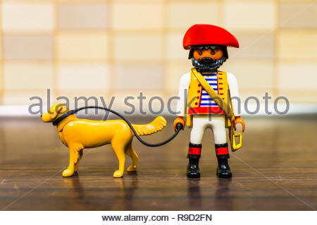 Poznan, Poland - December 22, 2018: Playmobil toy pirate walking her dog out with a line in soft focus background.  - Stock Image