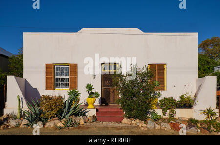 Traditional Karoo home architecture. White concrete facade with succulent garden. In Prince Albert, South Africa - Stock Image