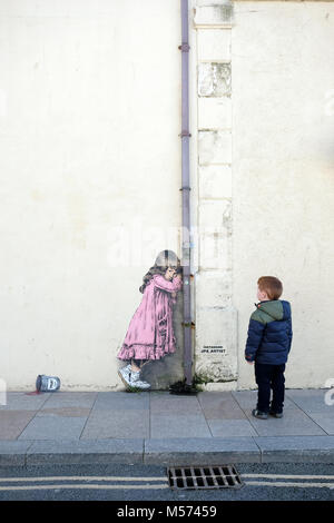 A young boy looks at a banksy style graffiti artwork of a young girl crying over a spilled tin of paint. The artworkby - Stock Image