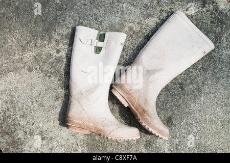 Dirty white wellingtons - Stock Image