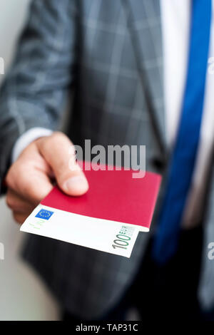 closeup of a young caucasian businessman, wearing an elegant gray suit, with his passport in his hand, with a 100 euros banknote in it - Stock Image
