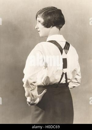 Side view of woman wearing suspenders and men's trousers, 1920s - Stock Image