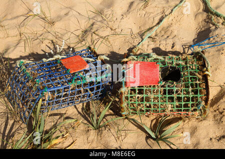 Two old and worn-out, hand made of iron and coloured plastic parts, crab traps washed away by tides and waves into - Stock Image