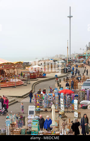 High angle shot of Brighton beach promenade with souvenir shops in the background and British Airways moving observation - Stock Image