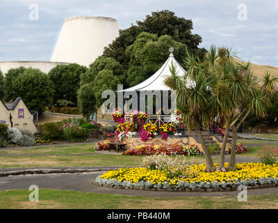 Summer bedding flowers in beds and round the bandstand in Runnymede Gardens, Ilfracombe, Devon, UK.  Landmark theatre in the background - Stock Image