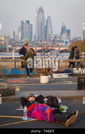 A protestor sleeps in the road on Waterloo Bridge for the Extinction Rebellion demonstration with the tower blocks of the City of London behind - Stock Image