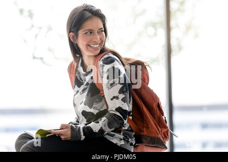 Female university student sitting on table in university lobby looking over her shoulder - Stock Image