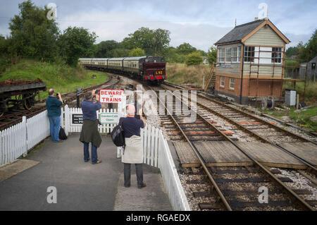 Train enthusiasts photograph a steam train of the South Devon Railway as it arrives at Ashburton Junction near Totnes, Devon - Stock Image
