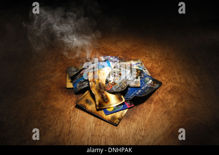 A pile of burnt credit cards with trails of smoke - Stock Image