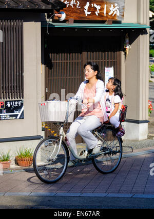 It's common to see two people riding a single bicycle in Japan - especially mothers & young children. Japanese - Stock Image