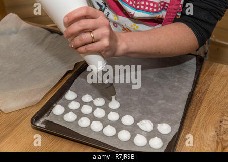 Woman making homemade meringues in a private kitchen - Stock Image