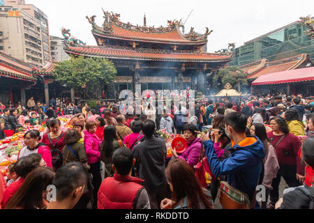 Smoke spreads around Longshan Temple in Taipei on Lunar New Year's Day as visitors burn incense and pray to mark he arrival of the Year of the pig. - Stock Image