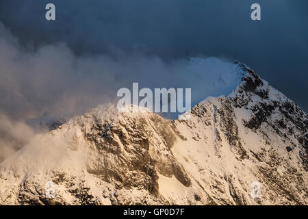 Snow blows from summit of mountain peak, Lofoten Islands, Norway - Stock Image