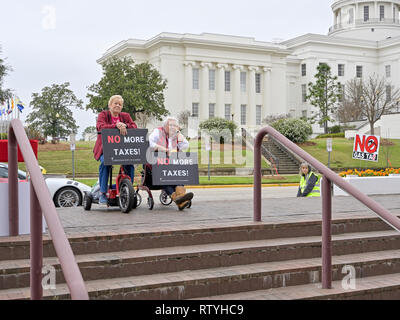 Two elderly or senior women in wheelchairs carrying signs for no more taxes listen to a speaker protesting higher higher gas taxes in Alabama, USA. - Stock Image