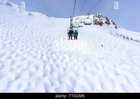 Unidentifiable skiers on chairlift going up a ski slope in the snowy mountain range of the Canadian Rockies, while skiers going down a mogul hill belo - Stock Image