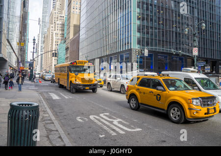 New York City Street with Municipal School Bus & Iconic NY Taxi Cab - Stock Image