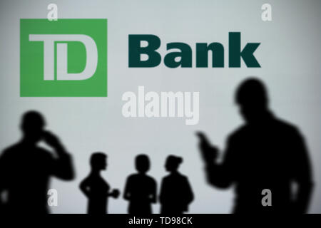 The TD Bank logo is seen on an LED screen in the background while a silhouetted person uses a smartphone in the foreground (Editorial use only) - Stock Image