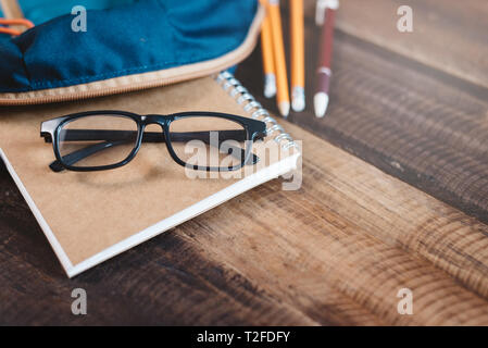 school bag, notebook,pencil,pen and eyeglasses on a wooden table.concept of school equipment and education. Selective focus on eyeglasses - Stock Image