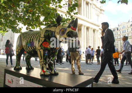 London, UK. 2 1 August 2018. Tourist seen by St Paul's Cathederal in the background of Rhino​ ​Marjorie painted by Eileen Cooper, at  Paternoster Square / St Paul's, part of the 21 Tusk Rhino Trail installations on display in London. The rhinos, embellished by the internationally renowned artist will be on display until World Rhino Day on 22 September to raise awareness of the severe threat of poaching to the species' survival. They will then be auctioned by Christie's on 9 October to raise funds for the Tusk animal conservation charity. Credit: David Mbiyu / Alamy Live News - Stock Image