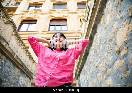 Happy young woman in pink sweater listening to music in the street. Low angle view - Stock Image