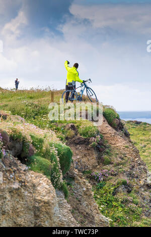 A cyclist standing with his bicycle and taking a selfie with his mobile phone on the edge of cliffs on the North Cornwall Coast. - Stock Image