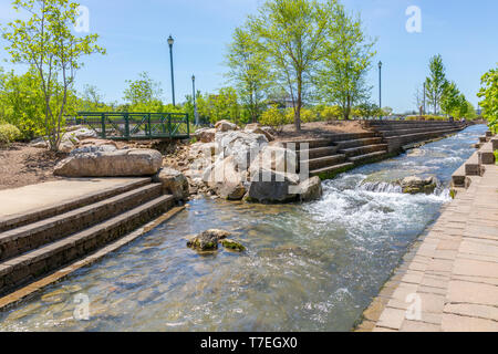 JOHNSON CITY, TN, USA-4/27/19: Masonry steps on both sides of stream flowing through Founders' Park in downtown. - Stock Image