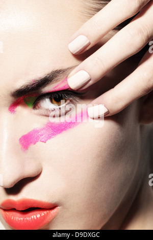Woman smudging bright coloured make up on face - Stock Image