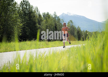 Front view of woman jogging on road - Stock Image