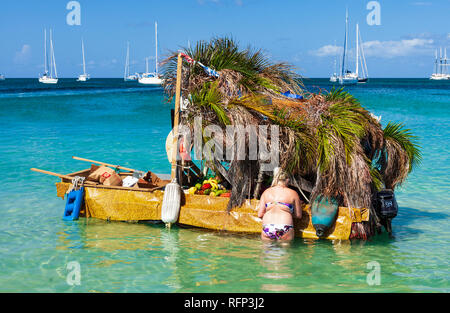 Woman making a purchase from a floating fruit shop shanty boat, Reduit Beach Rodney Bay, Saint Lucia, Caribbean. - Stock Image