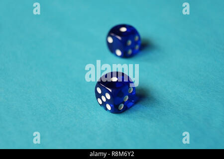 A vibrant monochromatic macro with depth of field about two blue glass gambling dice with two unlucky number one on blue background. - Stock Image