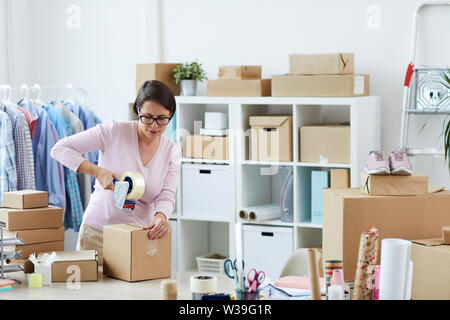 Young brunette woman sealing box with online order of client with cellotape while working in office - Stock Image