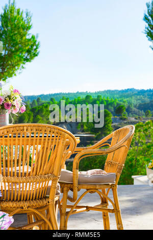 Terrace of luxurious white villa with wicker chairs table flowers bouquet on table fascinating view of valley mountains covered with green trees. Sunn - Stock Image