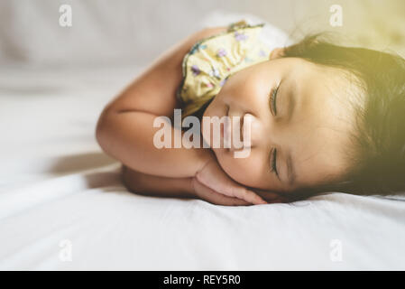 cute little asian toddler sleeping on her bed. concept of childhood and sleep - Stock Image