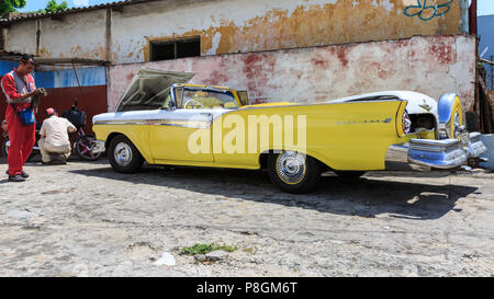 1957 Ford Fairlane 500 Skyliner convertible in yellow, American classic car being cleaned at a garage in Havana, Cuba - Stock Image