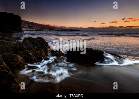 Beauty of the sea and beach in the evning dusk timeless scenic place in logn exposure - red coloured cludh beautiful sky in background - dark volcanic - Stock Image