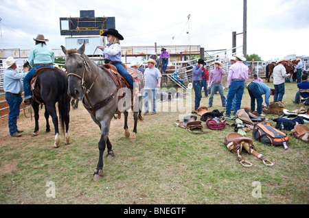 Cowgirl riding horse backstage at PRCA rodeo event in smalltown Bridgeport, Texas, USA - Stock Image