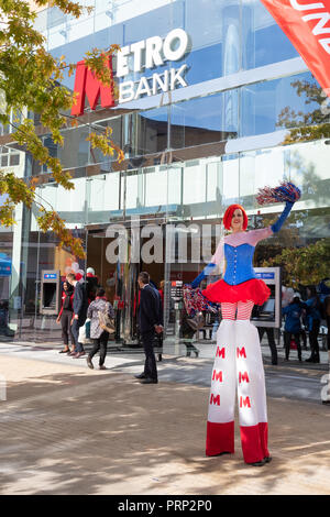 A new branch of Metro Bank opens in Broadmead, Bristol, UK. customers enter the bank as a cheerleader on stilts advertises the new branch is open - Stock Image