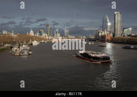 Looking eastwards (downriver) from Waterloo Bridge to the Southbank and the City of London, a burst of sunlight shines across river traffic, from the top of the One Blackfriars skyscraper, on 4th March 2019, in London England. - Stock Image