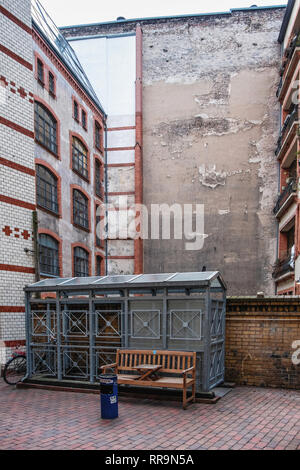 Mitte-Berlin. Inner Courtyard with brick building facade,weathered firewall, wooden bench & metal shed - Stock Image
