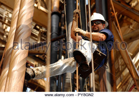 Worker in harness on offshore oil platform - Stock Image