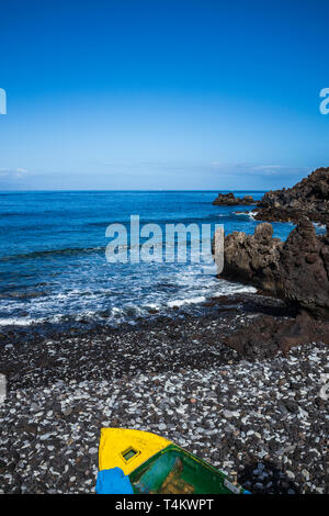 Old wooden rowing boat on a stony rocky beach in a cove at Fonsalia, Playa San Juan, Tenerife, Canary Islands, Spain - Stock Image