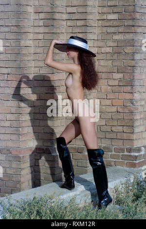 naked female naturist wearing sun hat and boots walking in the sunshine hungary 1980s - Stock Image