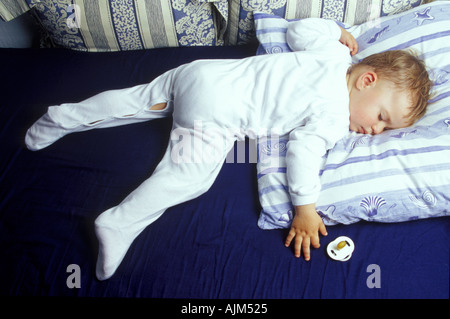 Sleeping baby boy on bed with pillow and white dress - Stock Image