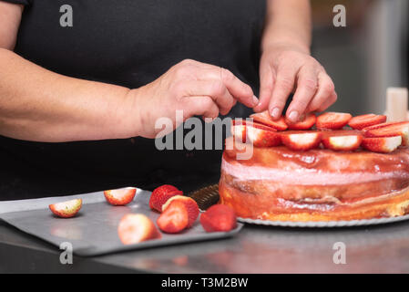 Close up of Professional confectioner making a delicious cake in the pastry shop . - Stock Image