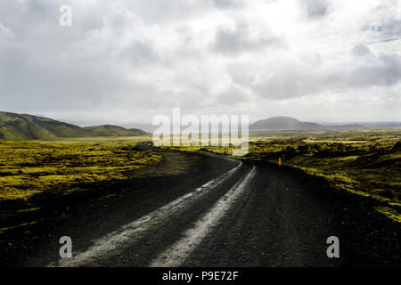 Icelandic lava landscape, road and distant mountains - Stock Image